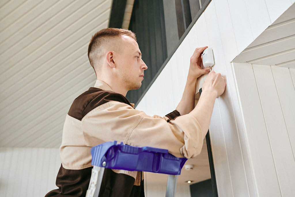 Man installing alarm system in home for security